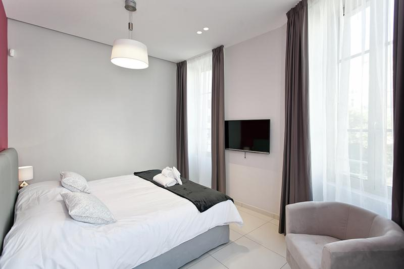 Double bedroom with white covers, a sofa chair, a tv and windows with view in Cannes