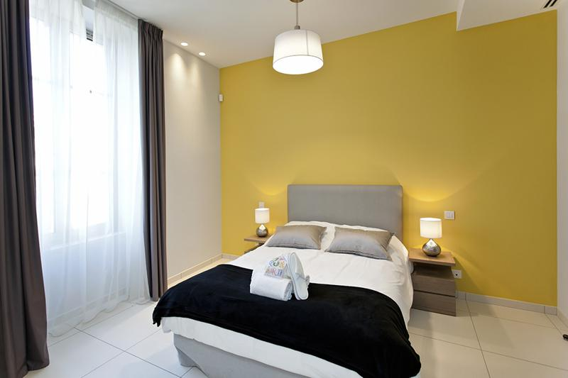 Yellow painted wall behind the double bed and a window with curtains in Cannes bedroom