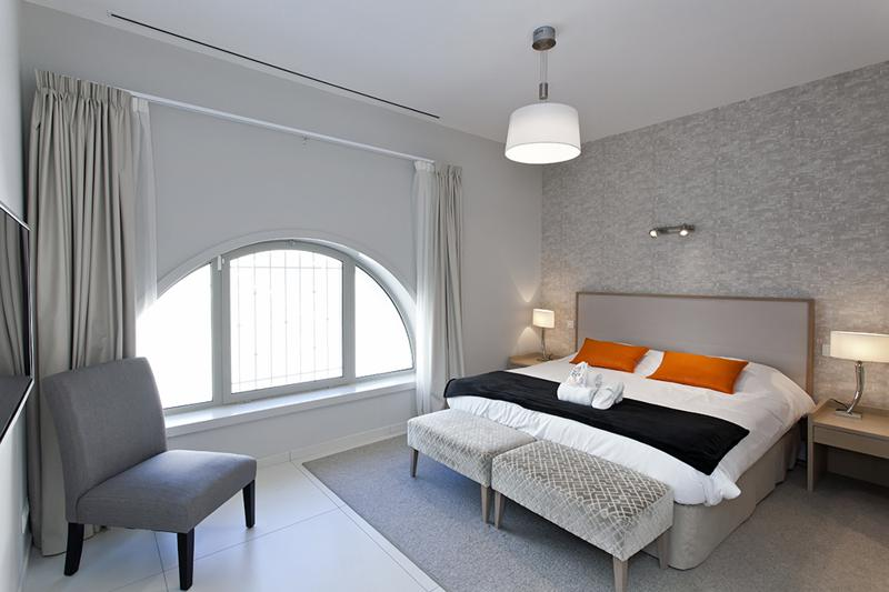 Double bed with stools, a corner chair and semi circular windows in a bedroom