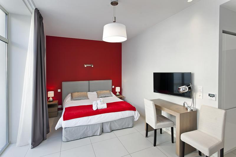 Red painted wall behind the double bed in a studio apartment with tv, desk and chair