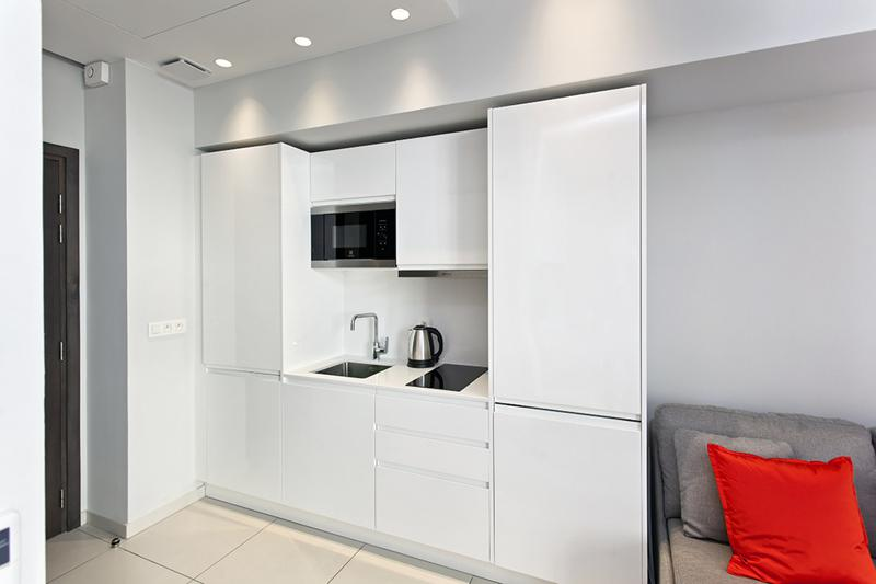Open kitchen with a coffee maker, a microwave and induction stove in a Cannes studio