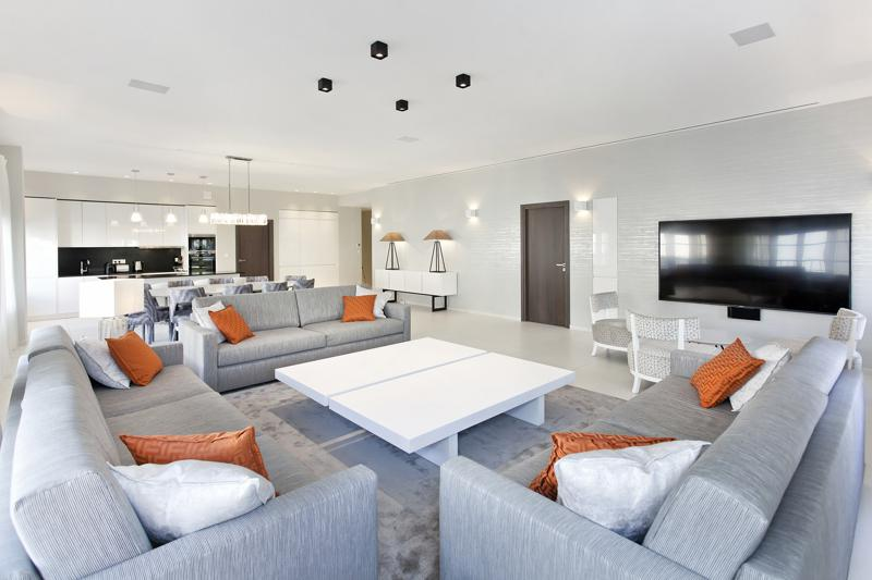 3 couch sets in the living room with flat screen tv, open dining area and kitchen in a Cannes group penthouse