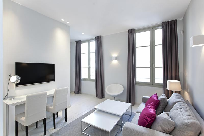 Living room with grey couch facing a wall mounted tv and brown window curtains in a Cannes rental apartment