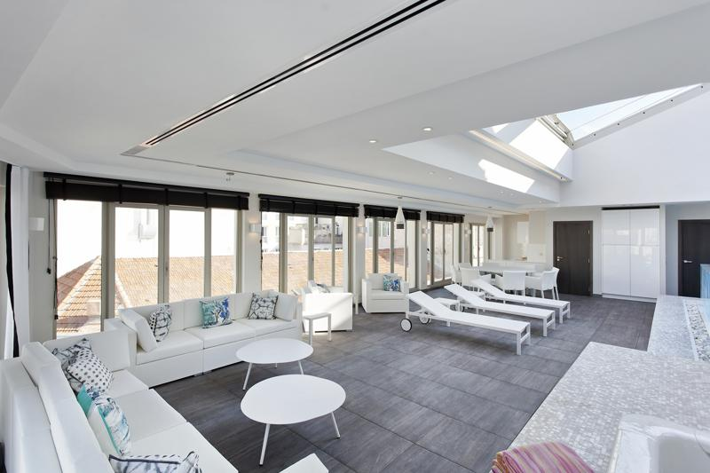 Covered rooftop with couches, lounge chairs and swimming pool in a Cannes penthouse for meetings and corporate events