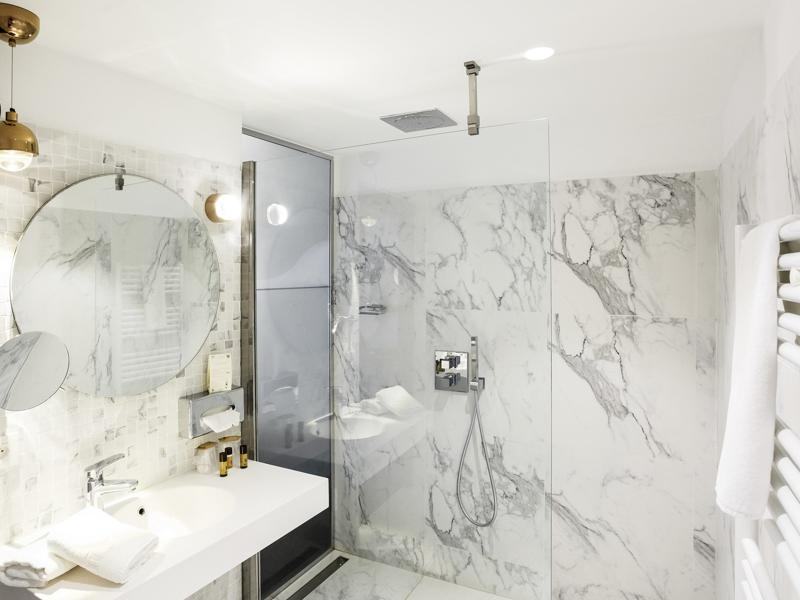 Bathroom with white marble tiles, a sink and a standing shower