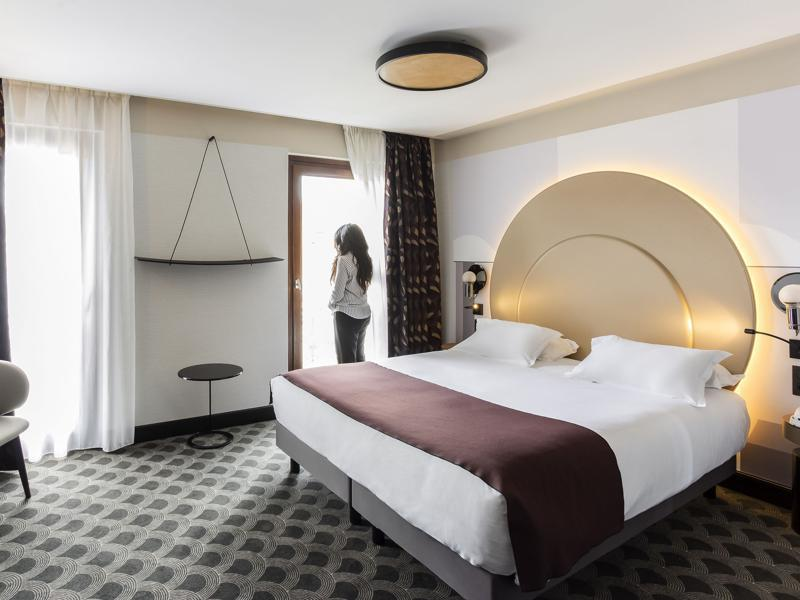 Double bed with a circular headboard and white and black window curtains in a rental room in Hotel Univers Cannes