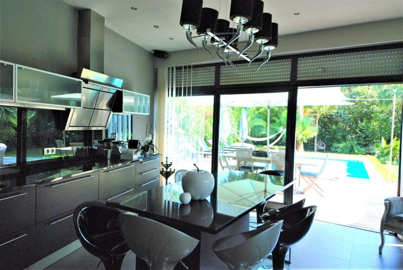 Dining table with bar stools next to the open kitchen with black countertops and cabinets in a Cannes event villa for groups