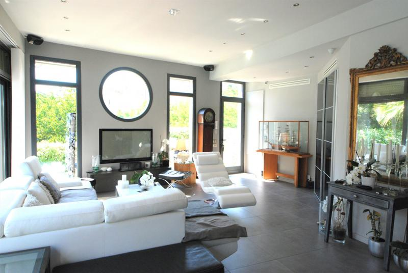 Floor standing clock and white couch sets in the living room with natural sunlight in a Cannes group villa with pool