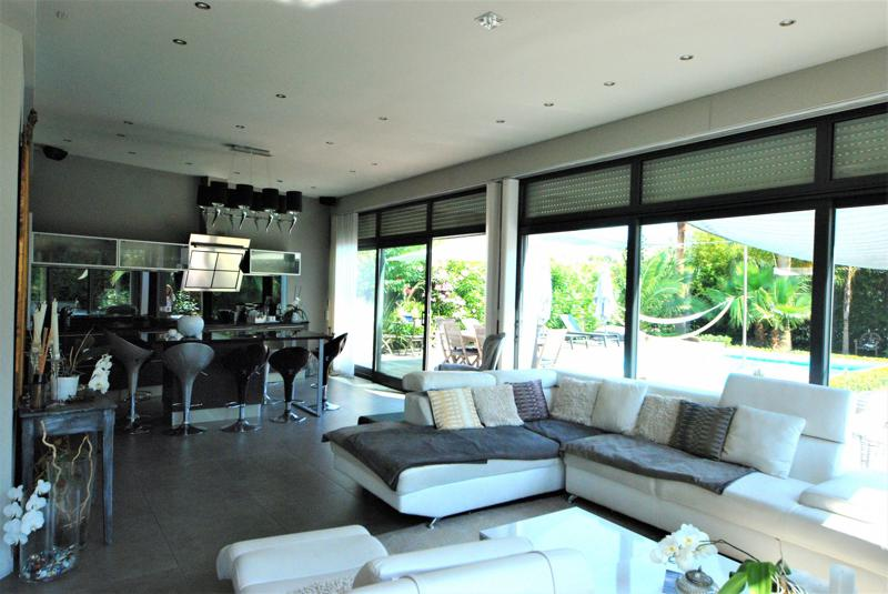 Living room of a Cannes corporate rental villa with white leather couches, black-themed open kitchen and outdoor garden views