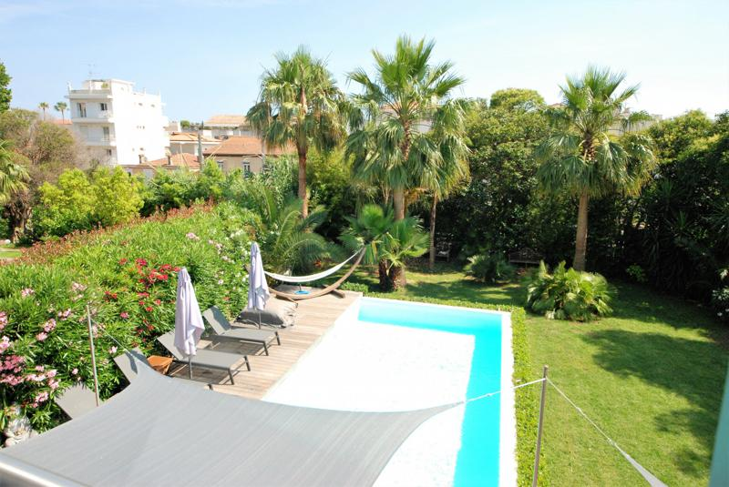 Top view of a Cannes event villa garden with palm trees, swimming pool and sunbathing chairs for parties