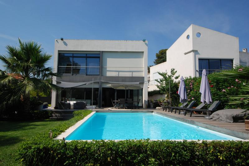 Garden with swimming pool, sunbathing chairs, couch sets and dining table for parties and events in a Cannes rental villa.