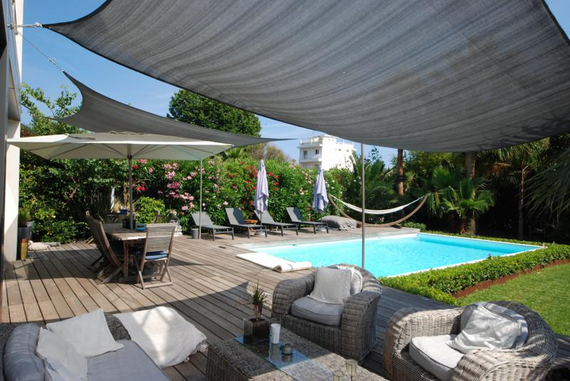 Outdoor patio furniture next to swimming pool with lounge chairs and hammock in the garden of a Cannes group villa for rent