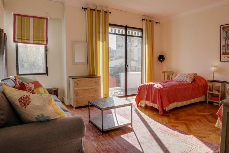 2 single beds in a room with wooden floor, carpet, table, couch and access to the balcony in a Cannes villa