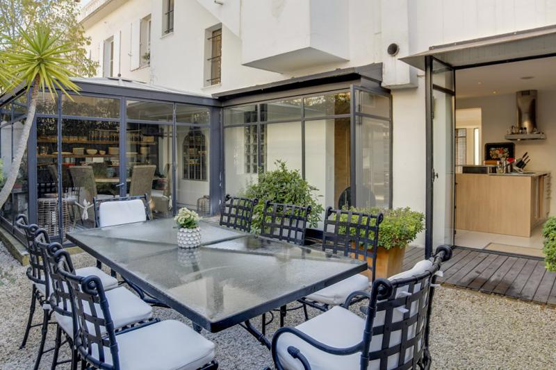 Dining table with chairs in an outdoor patio just outside the living room with pebble floor in a Cannes event Villa