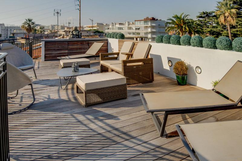 Rooftop deck with plants, chairs for sunbathing and views of city in a Cannes party villa