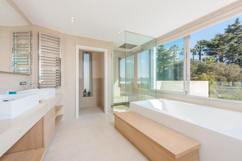Bathroom with glass walls and a bathtub in an exclusive Cannes rental villa with views