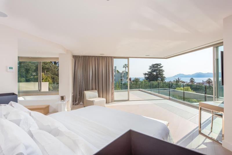 Bedroom with glass walls opening onto a spacious terrace with Mediterranean views in Cannes rental villa for groups
