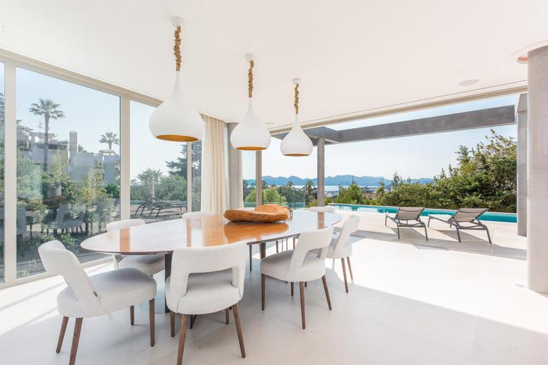 8 person dining table and lounge chairs for sunbathing next to the swimming pool with sea views in a Cannes villa for rent