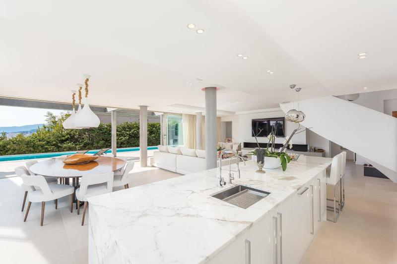 Open kitchen and a round table for meeting next to the swimming pool overlooking the sea in a 4 bedroom Cannes rental villa