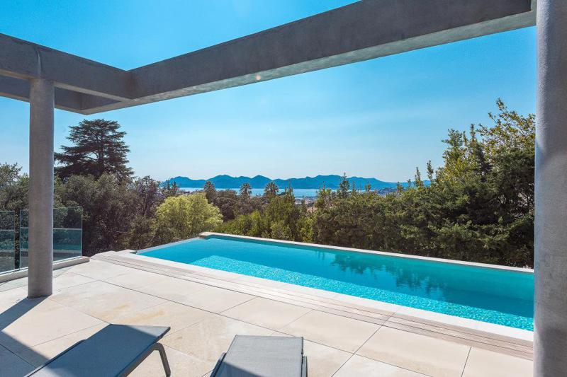 Lounge chairs next to the swimming pool with panoramic Mediterranean views in an East Cannes party villa for rent