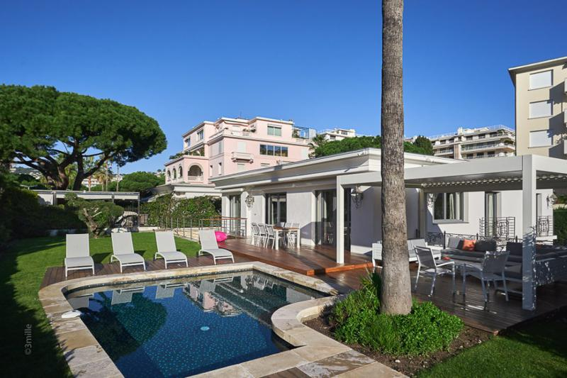 Outdoor deck with a lounge sitting and a swimming pool in a Cannes group party villa on Croisette de la Boulevard