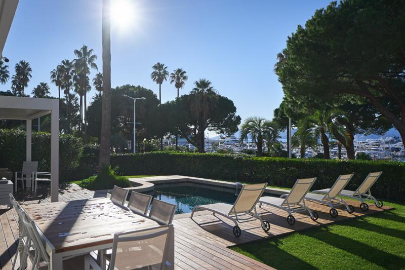 Sundeck with a swimming pool in the garden of a Cannes rental villa with sea and port views