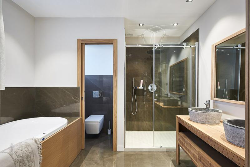 Bathtub and a glass-enclosed standing shower in a bathroom with a separate toilet in a Cannes villa