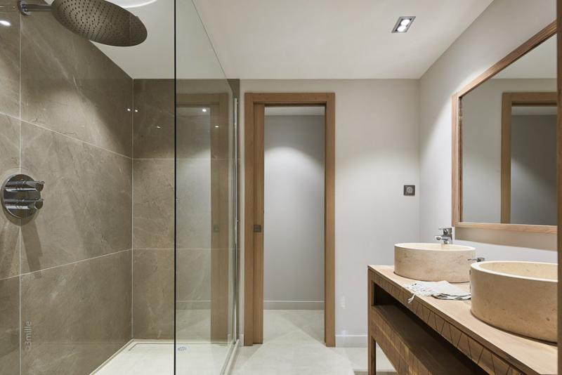 Standing shower and circular sinks in a bathroom