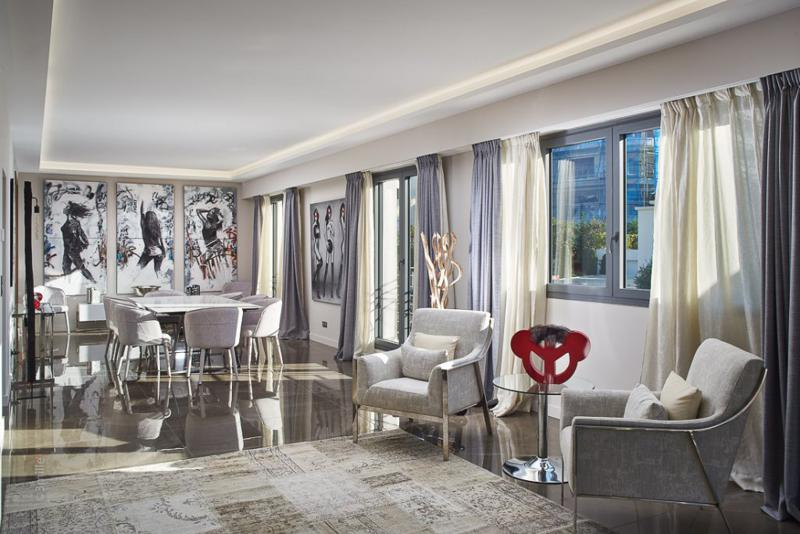 Living room of a Cannes group villa on the port with dining table, artistic paintings and interiors