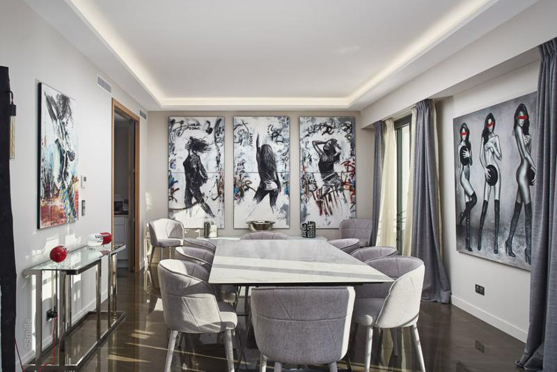 Paintings mounted on the walls of a dining room in an artistic Cannes rental villa