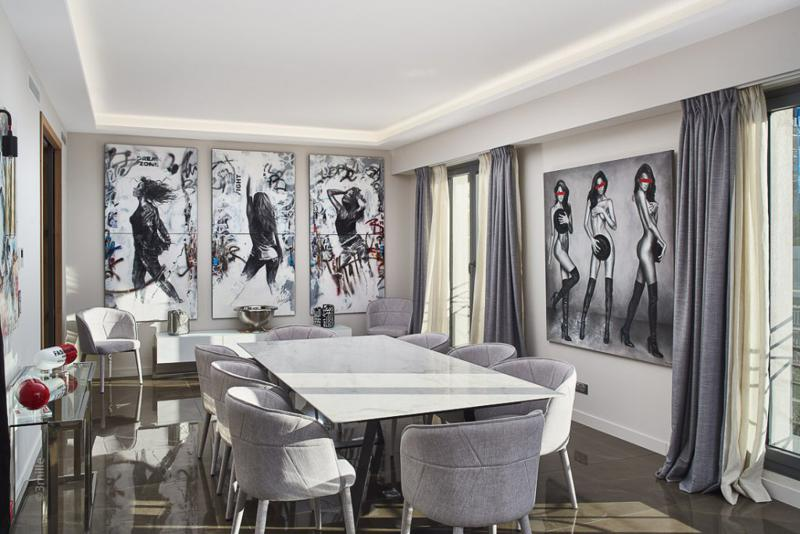 Wall paintings and dining table in the centre of a room with natural sunlight in a Cannes villa