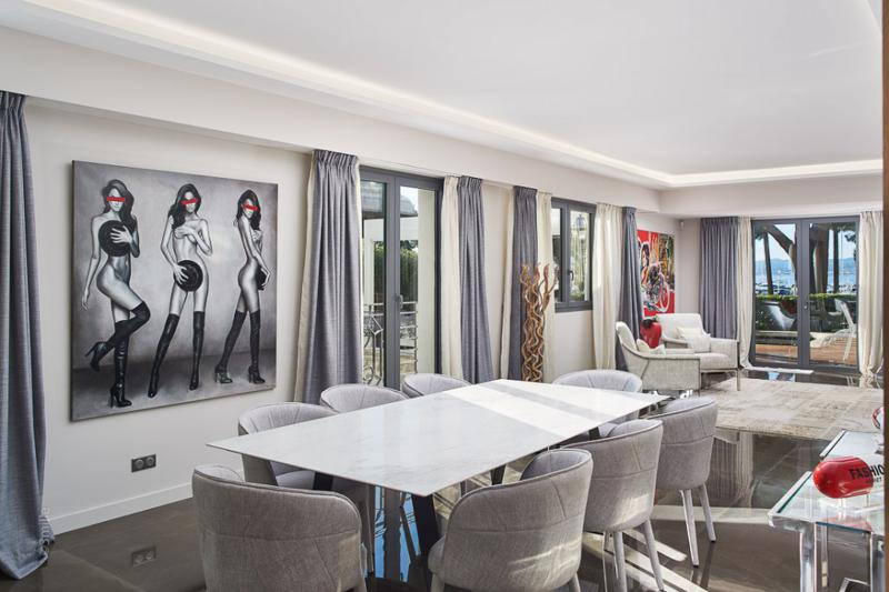 Dining table in the living room with glass doors overlooking the outdoor deck and garden in a Cannes group event villa