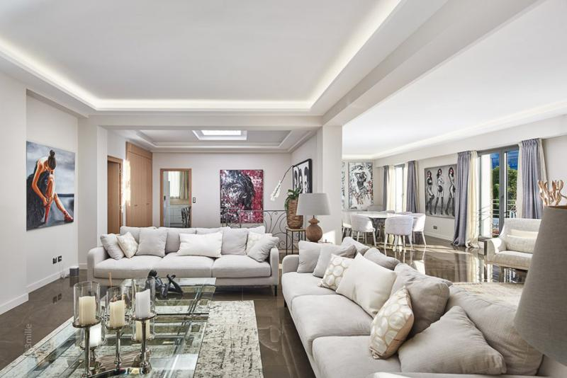 Cream couches and candle stands in a living room decorated with paintings in a Cannes event rental villa