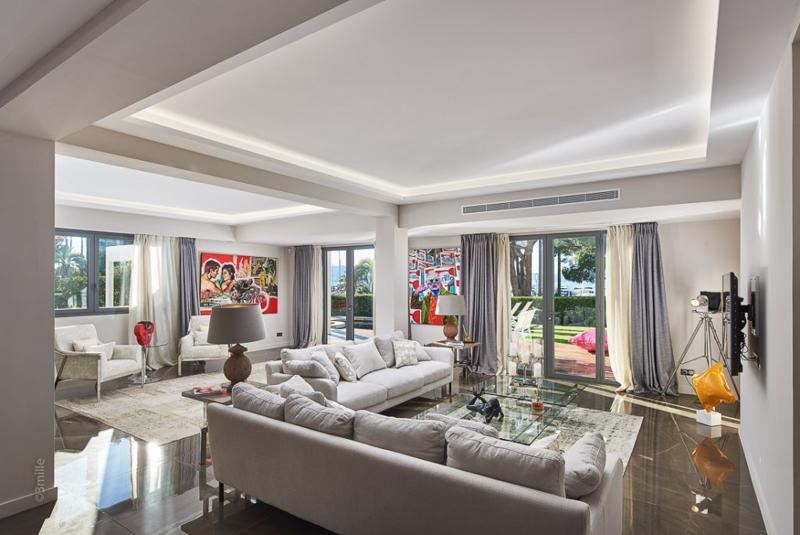 Views of port, garden and swimming pool from the living room of a Cannes group beach villa with cream couches