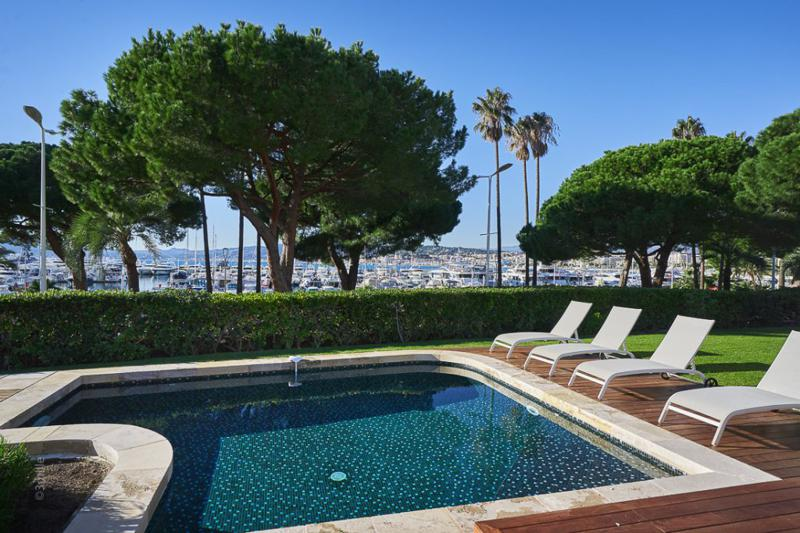 Swimming pool surrounded by lounge chairs on the deck for sunbathing and view of port and Mediterranean from a Cannes villa