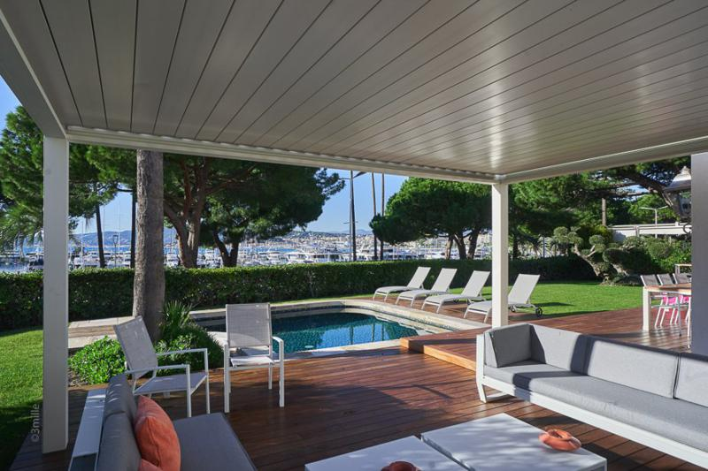Front deck with couches and chairs next to the pool in a Cannes beach villa with sea views