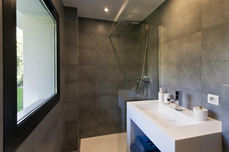 Bathroom with standing shower, white sink and brown tiles