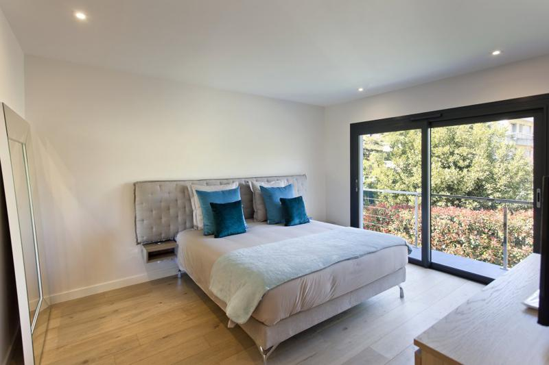Wooden floored double bedroom with a large mirror next to a wall and a terrace with a view in Cannes