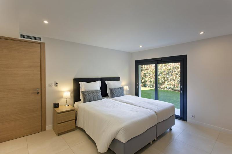 2 single beds with white blankets and pillows joined to make a double bed in a ground floor room in a Cannes villa