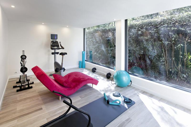Gym room with equipments, weights and cycling machine in a Cannes group event villa