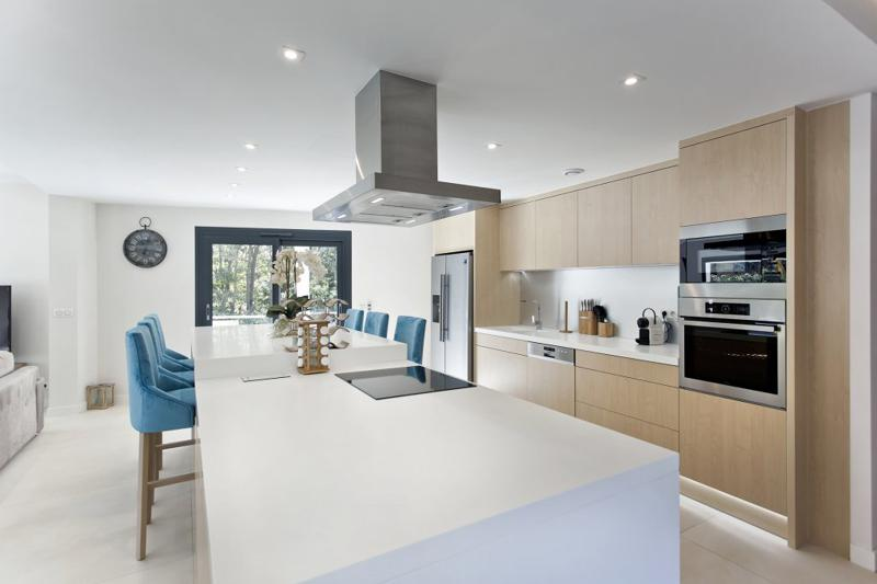 Open fully equipped kitchen with white countertop and silver hood exhaust in Cannes