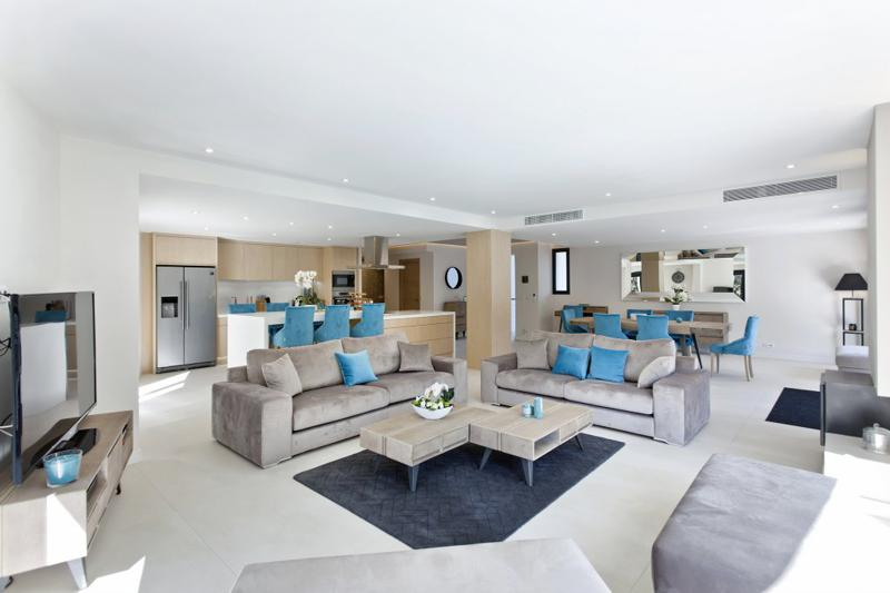 Living room with beige couches, open kitchen and dining area for meetings in a Cannes group villa
