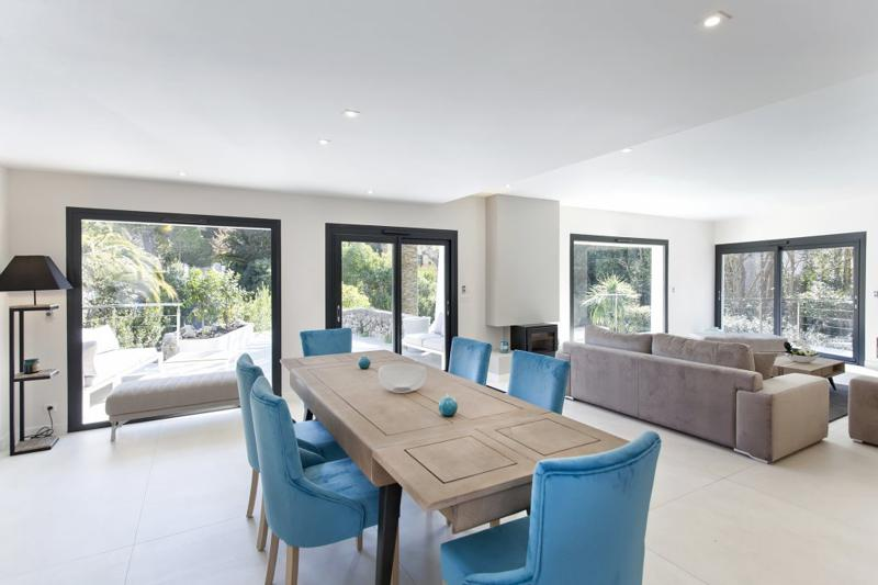 Wooden dining table with blue chairs in the dining area with a garden view from Cannes rental villa