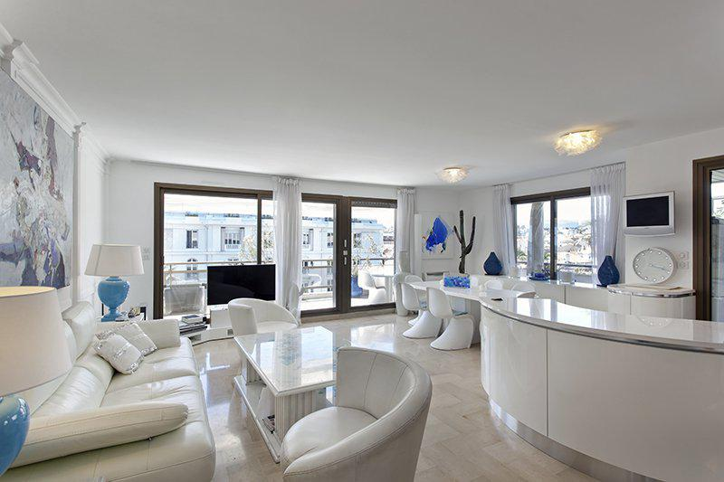White interiors in the living room and access to a terrace with outdoor furniture and views in a Cannes rental apartment