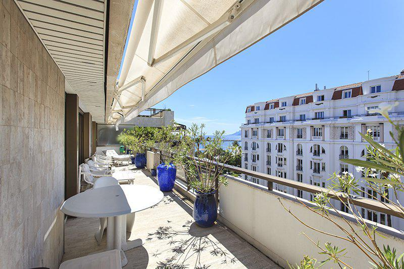 Terrace with lounge chairs for sunbathing and views of Mediterranean in a Cannes luxury group apartment