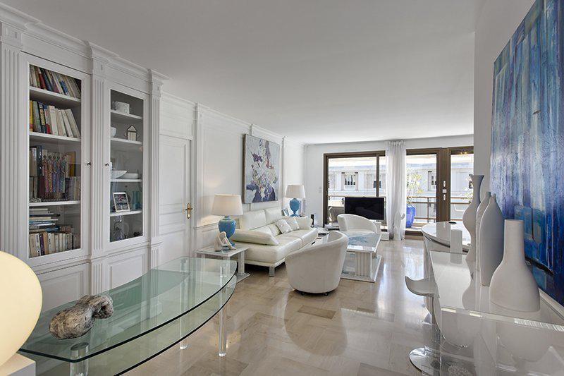 Book cabinet with glass door in the living room with couches and tv of a Cannes event accommodation on Gray d´Albion