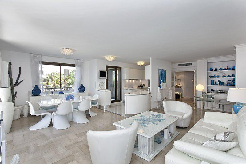 Living room with an open kitchen and meeting room overlooking terrace through windows in Cannes central party accommodation