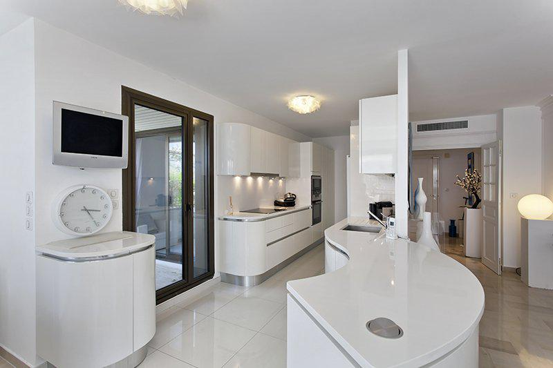 Open kitchen with a tv and white counters in Cannes