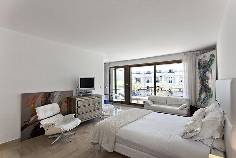Double bedroom facing a tv and a couch and a chair in the bedroom with access to terrace in a Cannes group accommodation