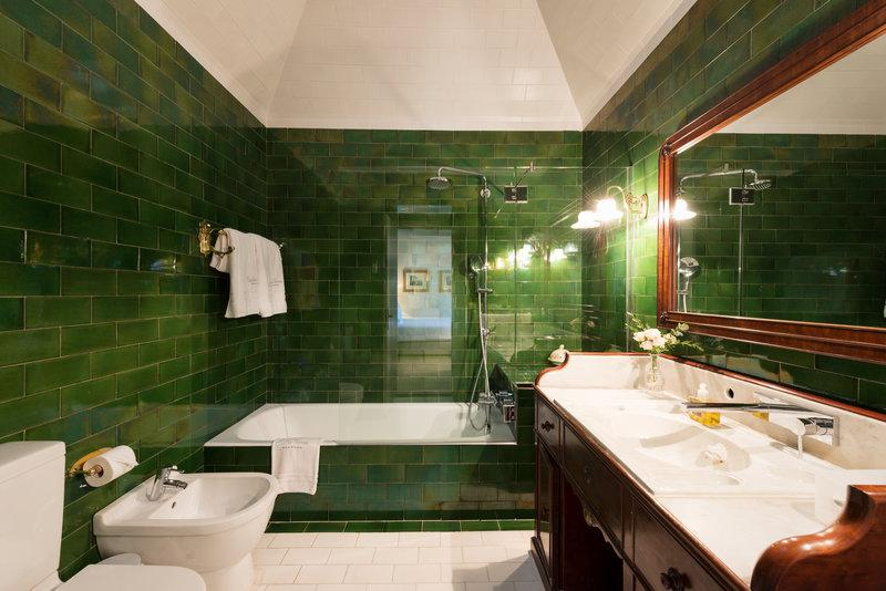 Bathroom with green tiles, a bathtub and a sink with a mirror over it in Barcelona